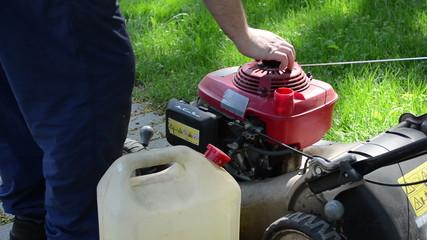 gardener hand open and fill empty lawn cutter mower fuel tank