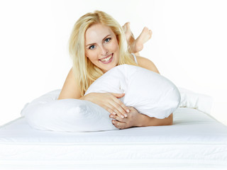 Woman cuddles her pillow in the morning