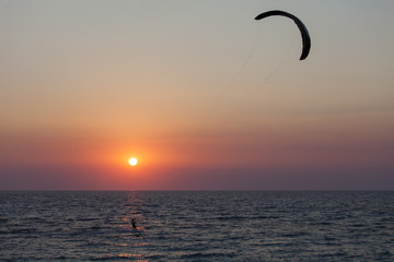 Silhouette of a kitesurfer sailing at sunset