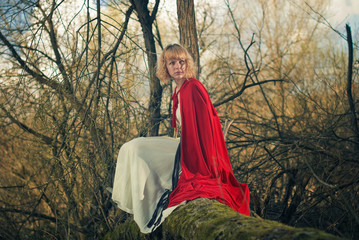 woman in red cape sitting at fallen spring forest tree