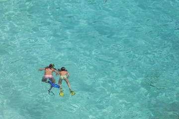 Two girls swimming while wearing snorkeling gear in water