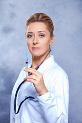 Female doctor with injection and stethoscope