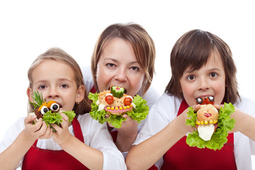 Woman and kids taking a bite from creative sandwiches