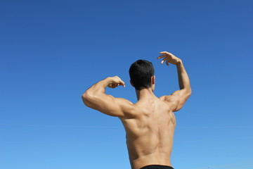 Muscle young man showing his back muscles