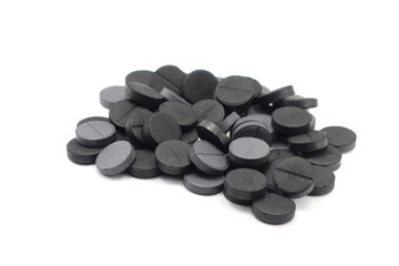 a handful of tablets of activated charcoal on white background