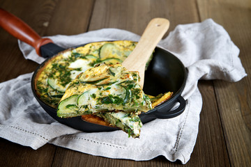 Scrambled eggs with onions, zucchini and herbs. Selective focus