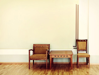 Two chairs and table near the wall