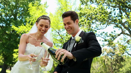 Newlyweds drinking champagne in the countryside