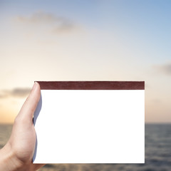 white blank notebook in woman hand and sunset background