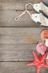 Toy fish with seashells and starfish on a wooden background