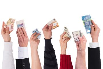 Viele Hände mit verschiedenen Währungen