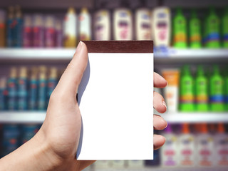 white blank notebook in woman hand and bottle background