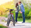 Two bicycles in front of young kissing couple in love blured in