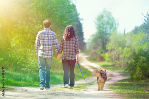 Young couple holding hands and walking with their dog in the vil