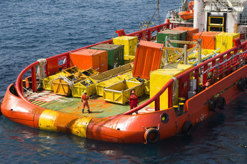 Seamen loading cargo onto a supply vessel