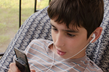 Teen boy listens music through headphones