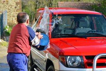 hombre mayor lanzando agua para lavar un coche rojo