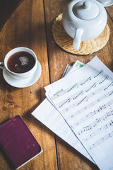 close up of sheet music and teapot