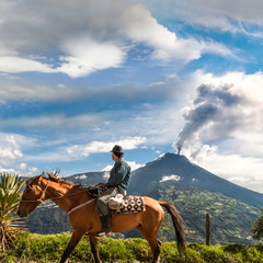 Unrecognizable farmer looking at the Tungurahua volcano eruption