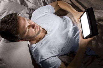 male in bed browsing the internet late at night with a tablet