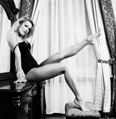 blonde with long legs posing next to the mirror