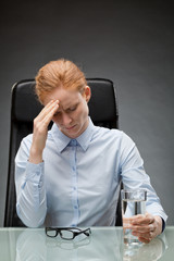 Overworked Businesswoman behind Desk