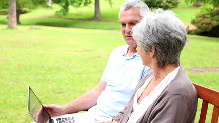 Retired couple sitting on a park bench using a laptop