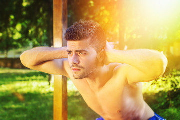 Shirtless man doing squats outdoors on sunny summer day