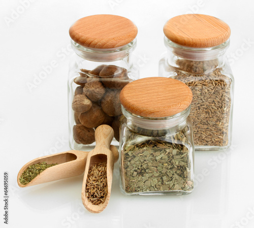 In de dag Kruiden 2 jars and wooden spoons with parsley, nutmeg and cumin isolated