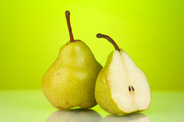 Ripe pears on bright green background