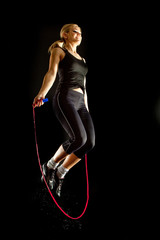 fitness girl jumps on a skipping rope