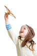 child girl dressed pilot helmet and playing with wooden airplane