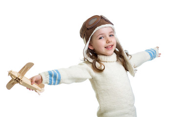 kid dressed as pilot and playing with wooden airplane toy isolat