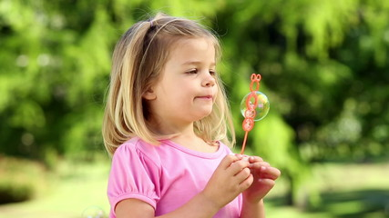 Little girl playing with bubbles in the park