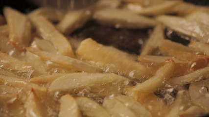 French fries cooking in boiling oil (with perforated spoon)