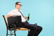 Businessman relaxing with a beer on blue background