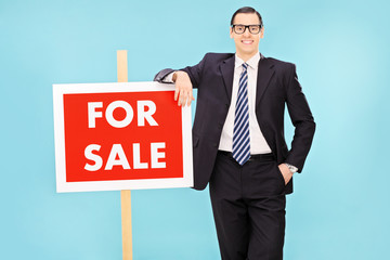 Businessman standing next to a for sale sign