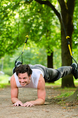 Fitness - Mann beim Suspension training im Park