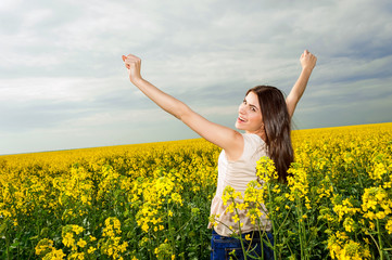 Happy young woman with hands in the air