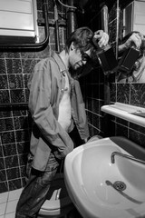 Drunk Man is standing in a toilet with a bottle of whiskey