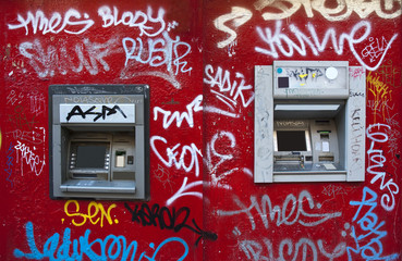 Cash machine in a graffiti red wall