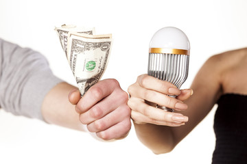 male and female hand holding LED bulb and money