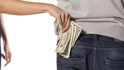 woman pulls money out of the pocket of the man's pants