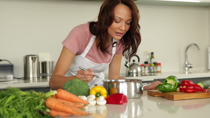 Woman stirring saucepan with lots of vegetables on counter
