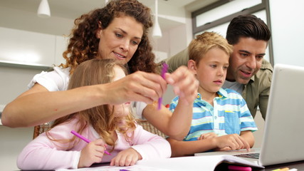 Cute children drawing at the table with their parents and using