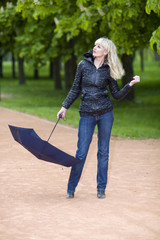 Young  woman walks on park in cloudy weather with an umbrella