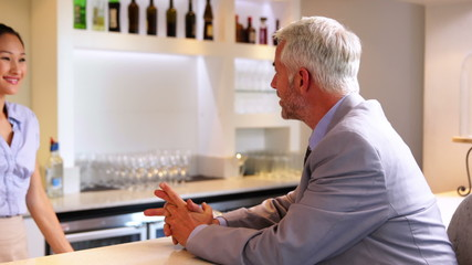Businessman ordering a drink from barmaid