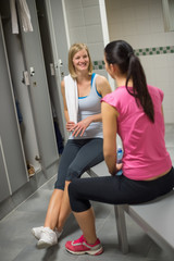 Woman sitting with friend in locker room