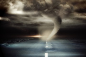 Stormy sky with tornado over road