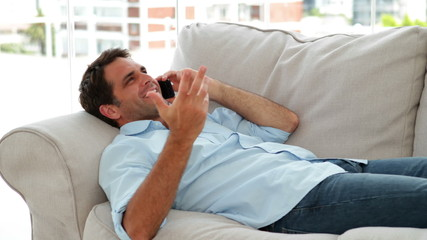 Casual man lying on the sofa chatting on the phone